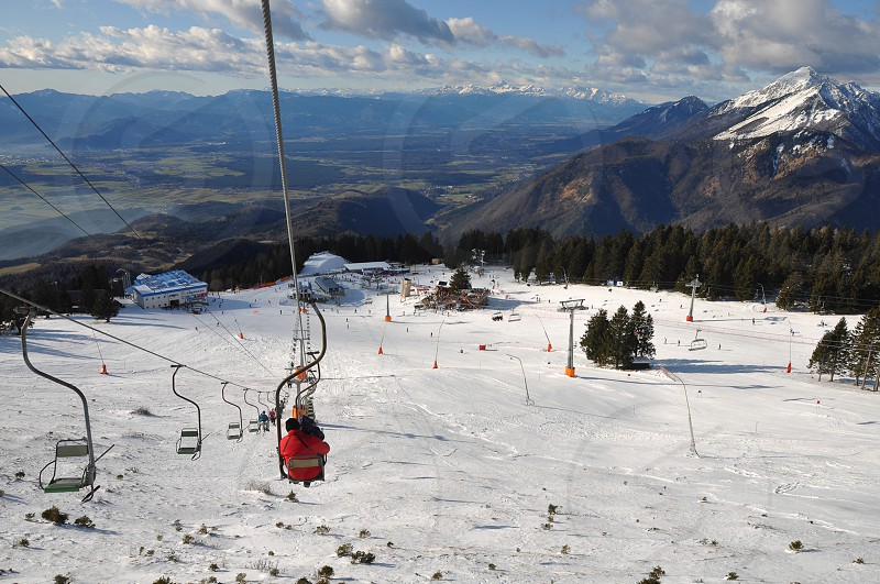 People riding a skilift at Krvavec Alpine Mountain Ski Resort in Slovenia panoramic view of ski piste and Julian Alps in background photo