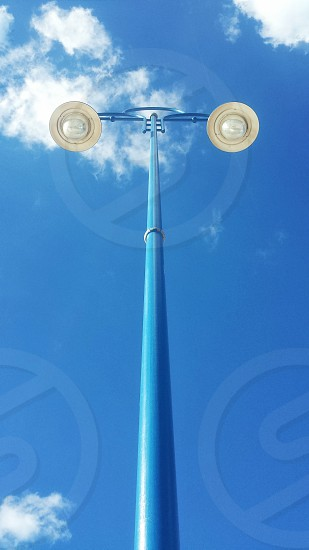 a blue and white double street light under a white cloud and clear blue sky during daytime photo