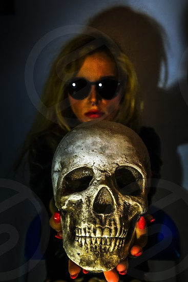 A beautiful girl with a skull between hands photo