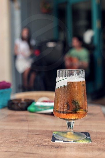 A glass of cold beer on a table with people behind photo