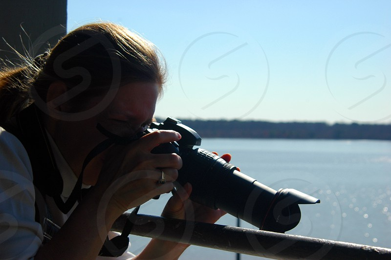 Woman photographing at a lake photo