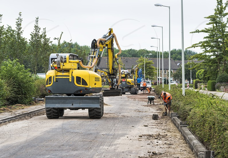 HellevoetlsuisNetherlands-12-July-2018:construction workers are busy n renewing the road in the villageone in a white the streets have to get new asphalt and will be closed for several weeks photo