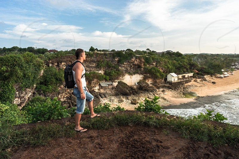 A man looking forward from the cliff. Balangan beach. Bali. Indonesia. photo