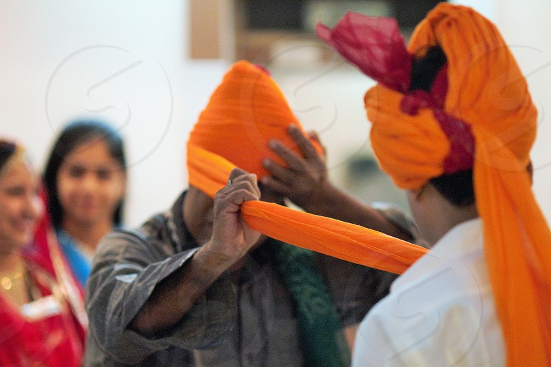 groom family preparing turbans for men wedding day Indian wedding tradition ceremony colors people photo