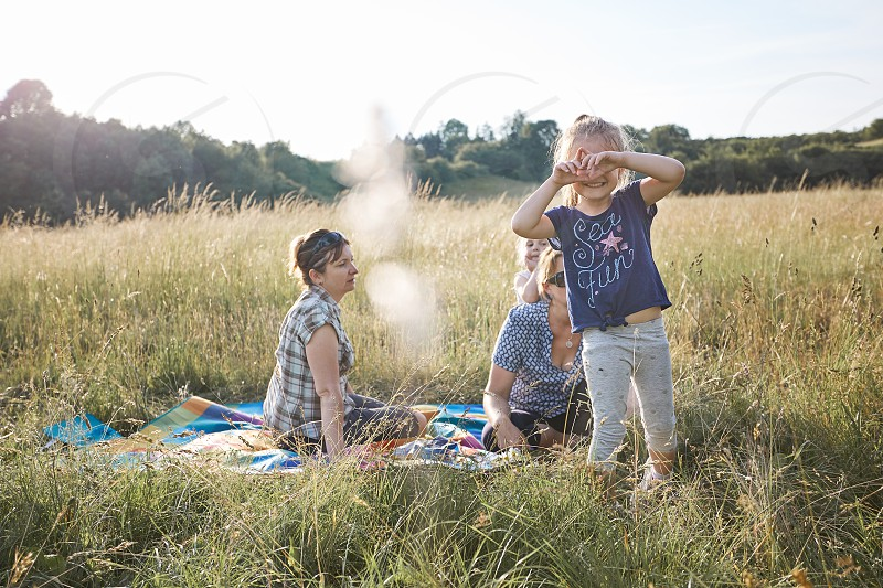 Little girl making a hand gesture for taking picture. Family spending time together on a meadow close to nature. Parents and kids sitting on a blanket on grass. Candid people real moments authentic situations photo