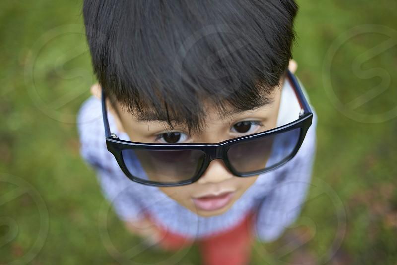 Fun portrait of a young Asian boy wearing big adult sunglasses photo