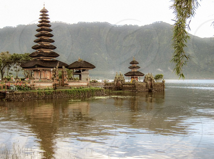 pagoda temple near body of water overlooking mountain under white sky during daytime photo