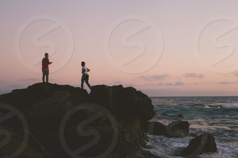 two people standing on rocky shore with sea in background below pink and gray sky during twilight photo