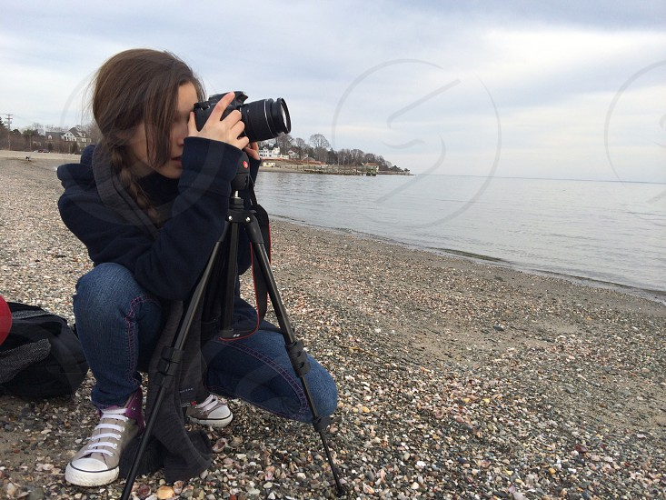 woman taking photo with a tripod on the shore of a lake photo