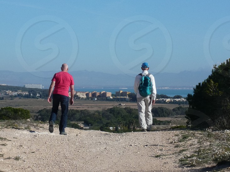 Two older male hikers enjoying the view company & fresh air near Torrevieja Spain photo