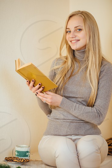 Young girl reading her book drinking coffee with cookies and smile to camera photo
