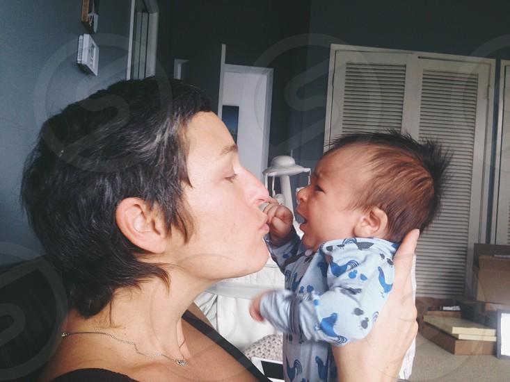 woman kissing infant photo