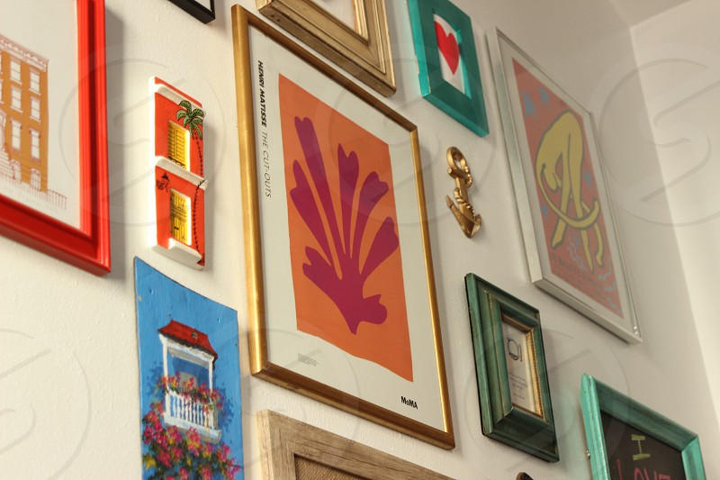 assorted-design paintings with frames on white wall photo