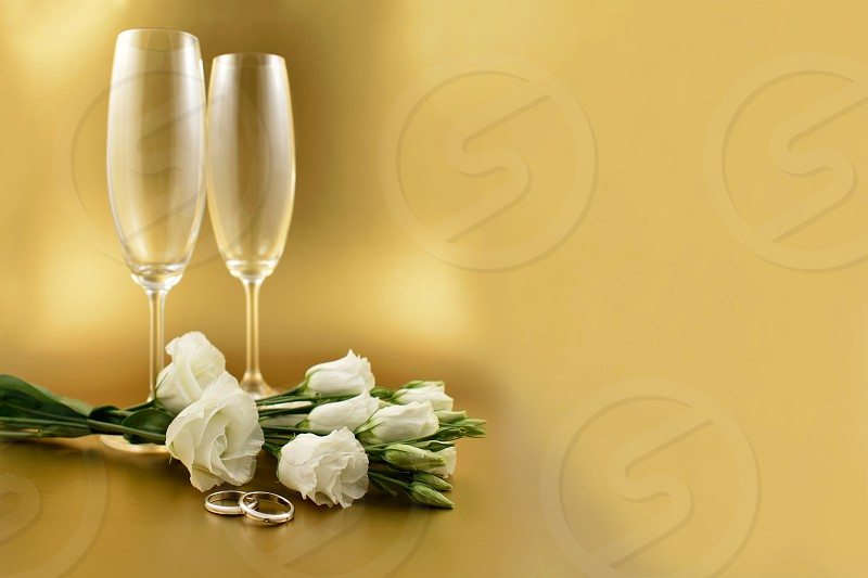 Wedding rings with white bouquet and champagne. Golden wedding background. White flowers with a rings. Valentines Day concept. White romantic bouquet images. Lisianthus Eustoma Grandiflorum. photo