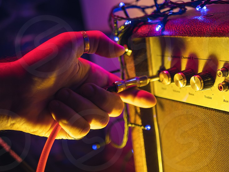 Man plugging jack into the guitar amplifier closeup for music entertainment themes. Neon colorful light photo