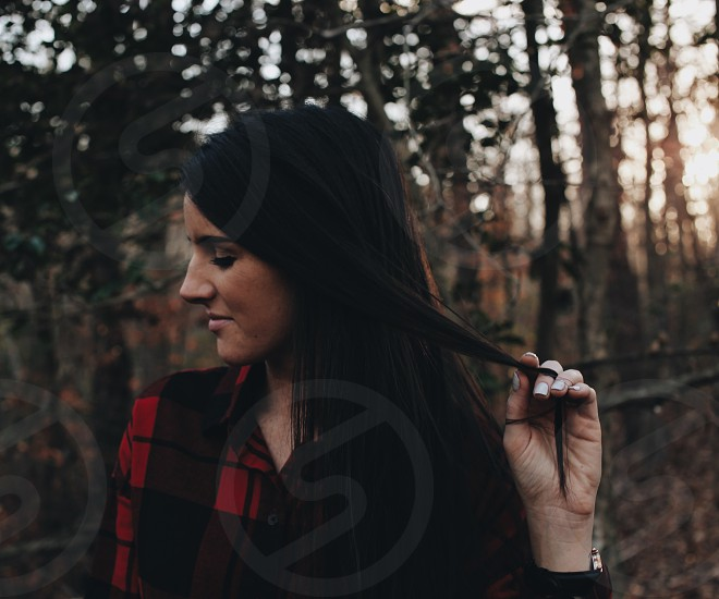 woman with black long hair in red and black button up shirt holding small strand of her hair in forest during daytime photo