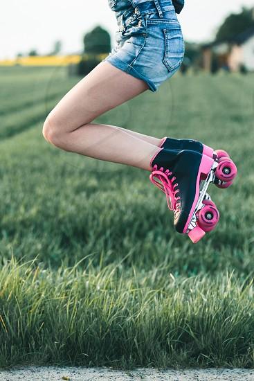 Teenage girl having fun rollerskating jumping spending time on summer day photo