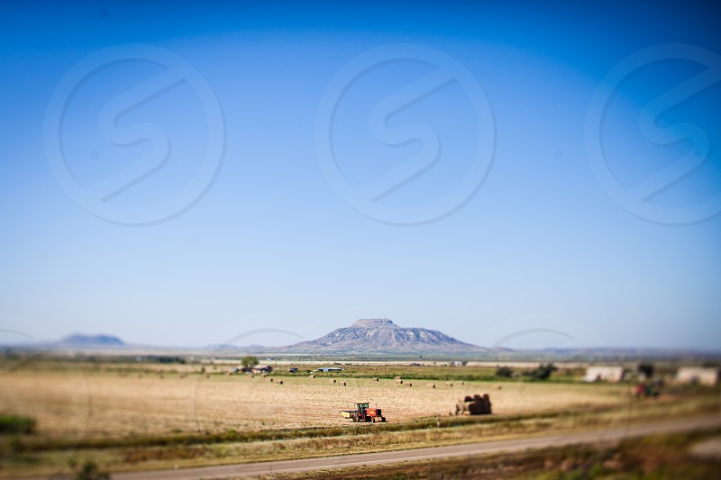 tractor on field behind hills under blue sky during daytime photo