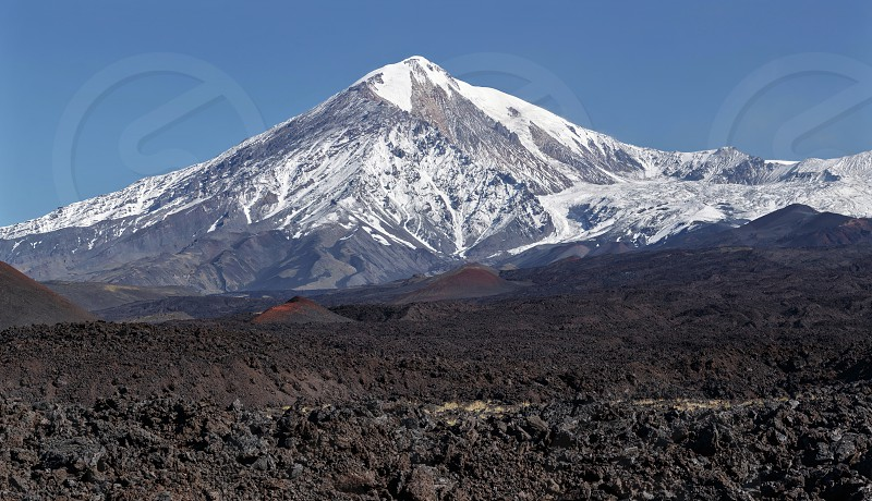 Beautiful volcanic landscape of Kamchatka: view on active Tolbachik Volcano. Panorama of the volcano on a sunny and cloudless day. Russian Far East Kamchatka Peninsula Klyuchevskaya Group of Volcanoes. photo
