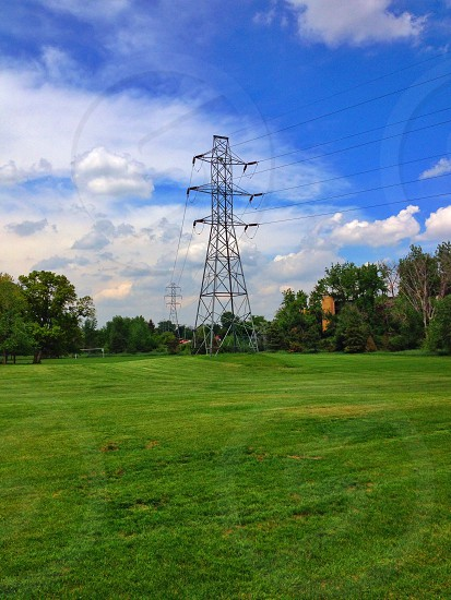 black electric tower on green rolling grass photo