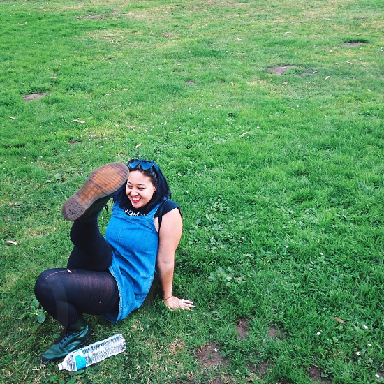 woman in blue tank top sitting on green grass photo