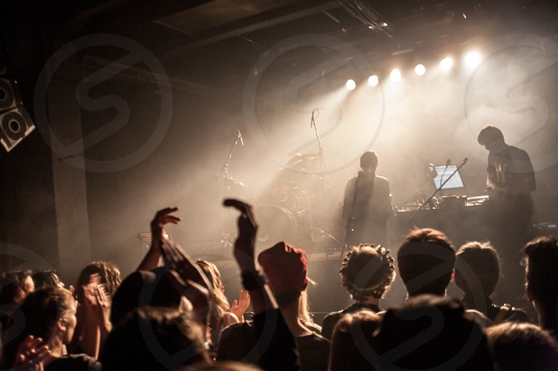 Fans with hands in the air and band at a live show photo