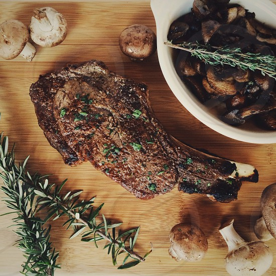 cooked steak on brown wooden board photo