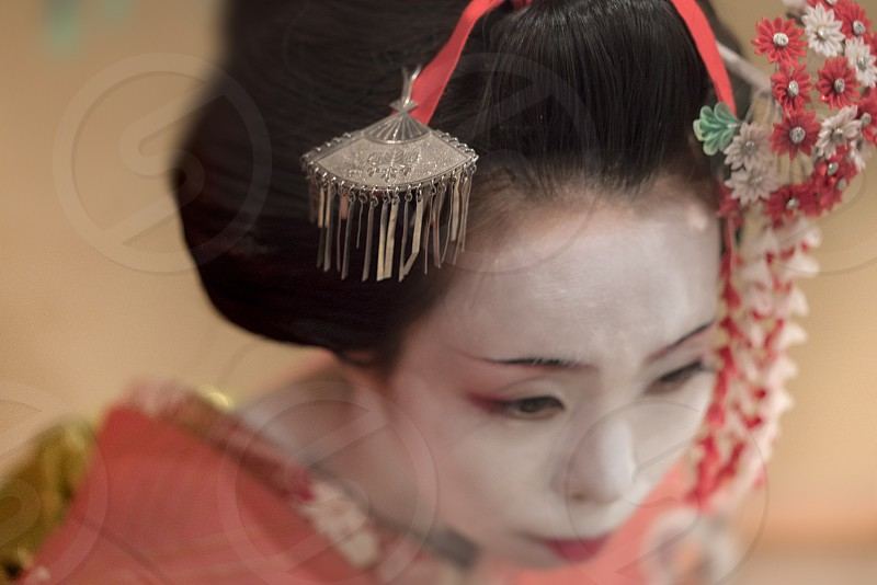 Japanese Maiko or geisha in red kimono coifed hair brooch with patterns of red and white plum blossoms photo