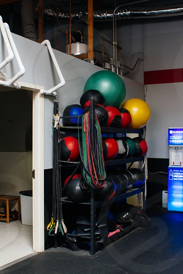 pile of exercise balls on black 4 tier shelf inside white painted wall room photo
