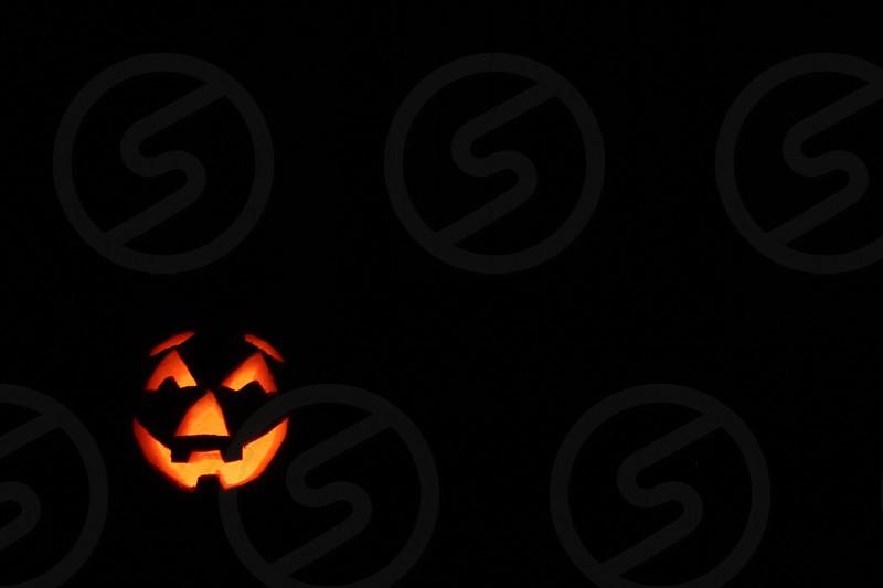 lit up jack-o-lantern in darkness photo