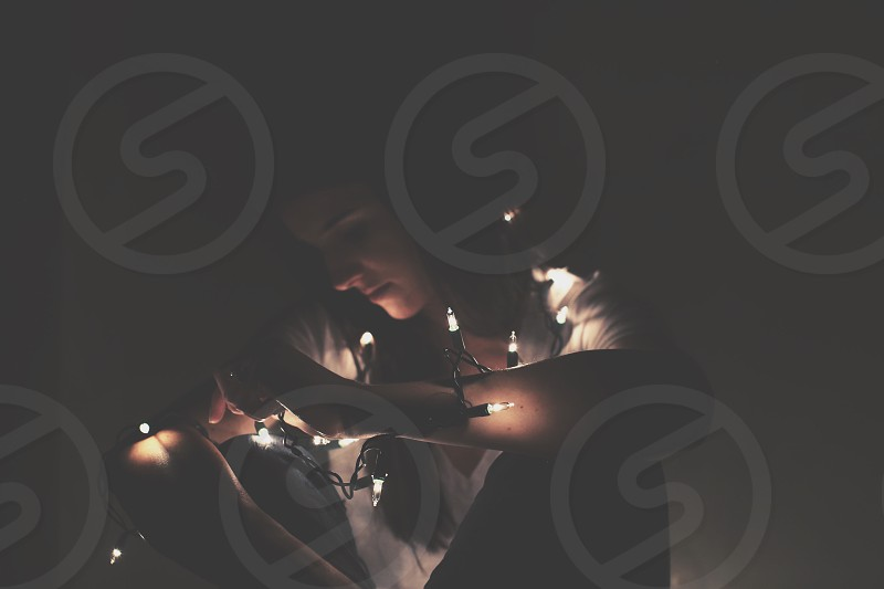 low light photography of a woman in white v neck shirt with string lights around her body photo