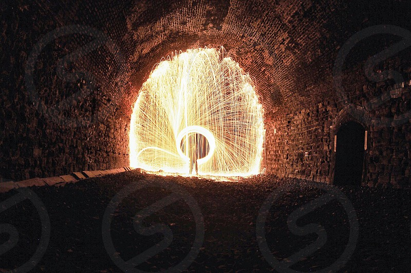 steel wool photography of men using fire crackers at the end of the tunnel road photo