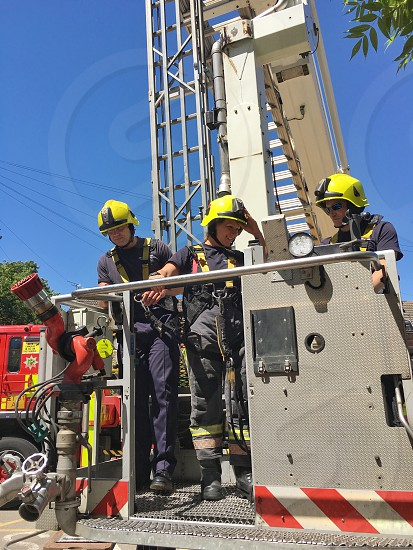Male and female Firefighters on high rise ladder photo