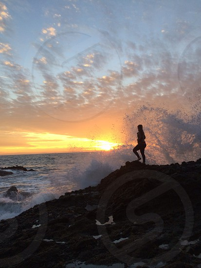 Silhouette of girl watching the waves break against rocks. photo