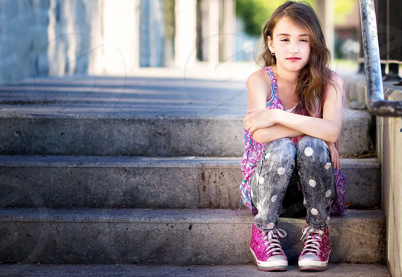 Girl with long hair and pink shoes sitting on stairs. photo