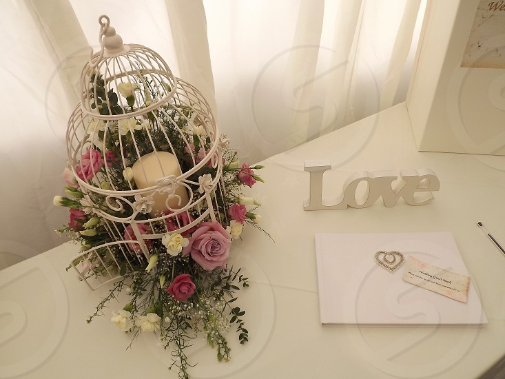 black wire decorative birdcage beside white Love letter cutout standee on white wooden table photo