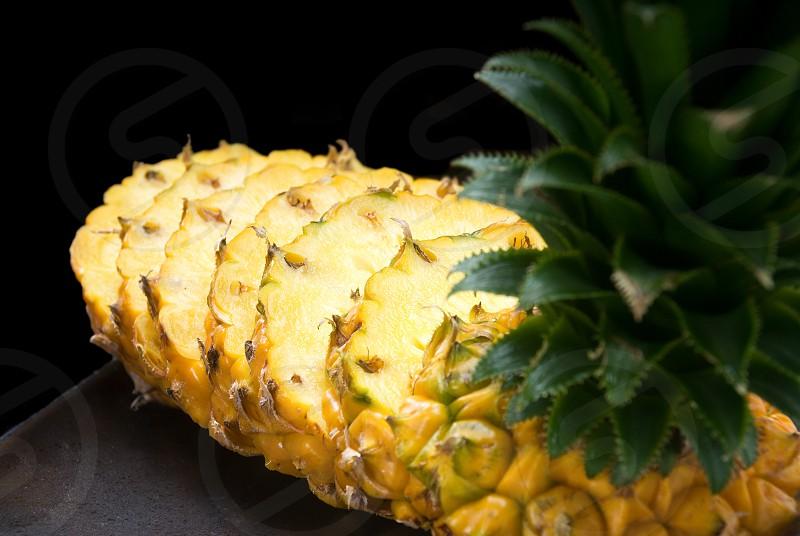 ripe vibrant pineapple sliced on a black plate photo