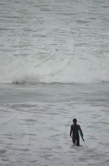 Boy walking into ocean photo