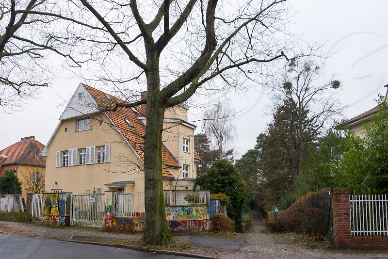 Small street between villas direct to Thielpark in the village around Thielpark inside Dahlem Neighborhood in Berlin Germany The Thielpark is a center which nice villas is located around.  photo