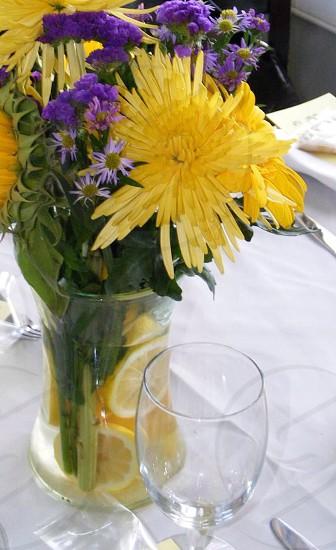 flowers in vase beside wine glass photo
