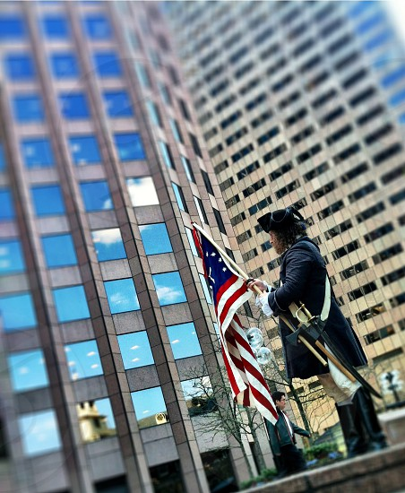 Freedom Trail guide rolling up flag. Downtown Boston. photo