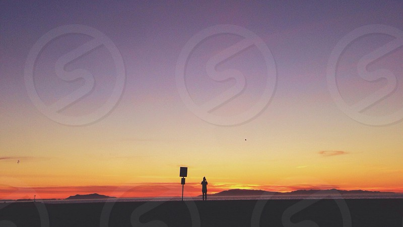 person standing watching the view of sunset  photo