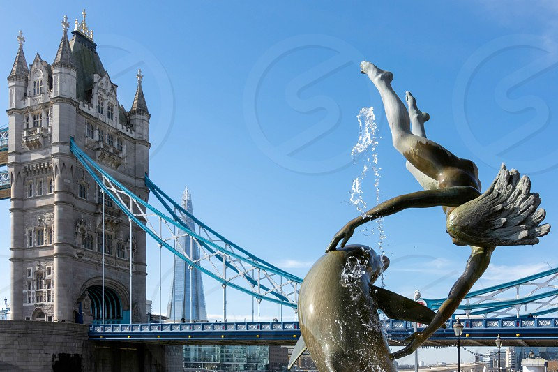 """David Wayne Sculpture """"Girl with the dolphin"""" next to Tower Bridge in London photo"""