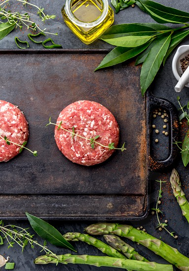 Raw meet ground beef burgers on cast iron frying board with asparagus herb oil and spices. Top view. photo