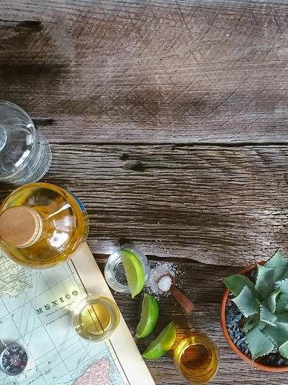 yellow tequila bottle beside a shot glass and lemons and salt on a brown wooden surface photo