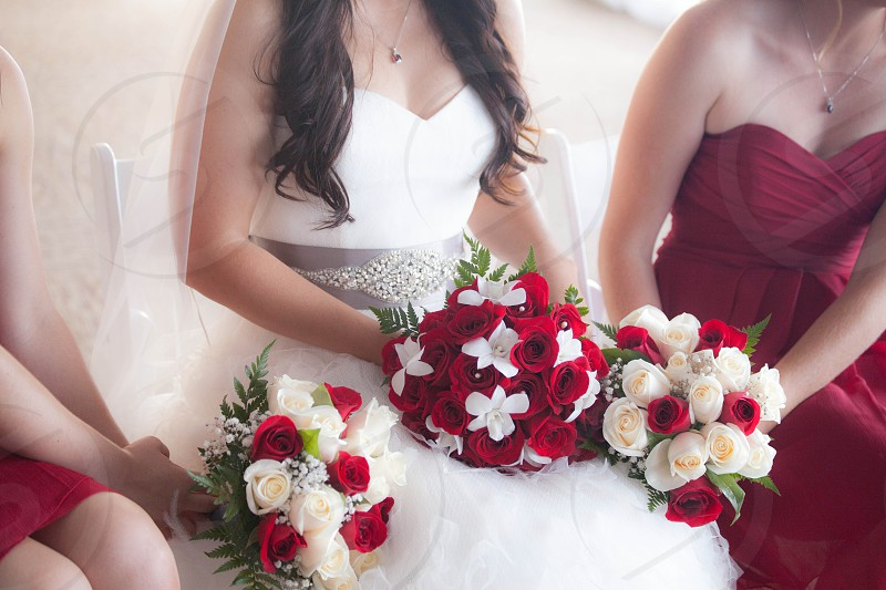 woman in white wedding dress beside woman in red gown  photo