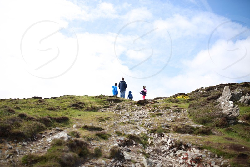 people standing on rocky hilltop under white cloudy sky photo