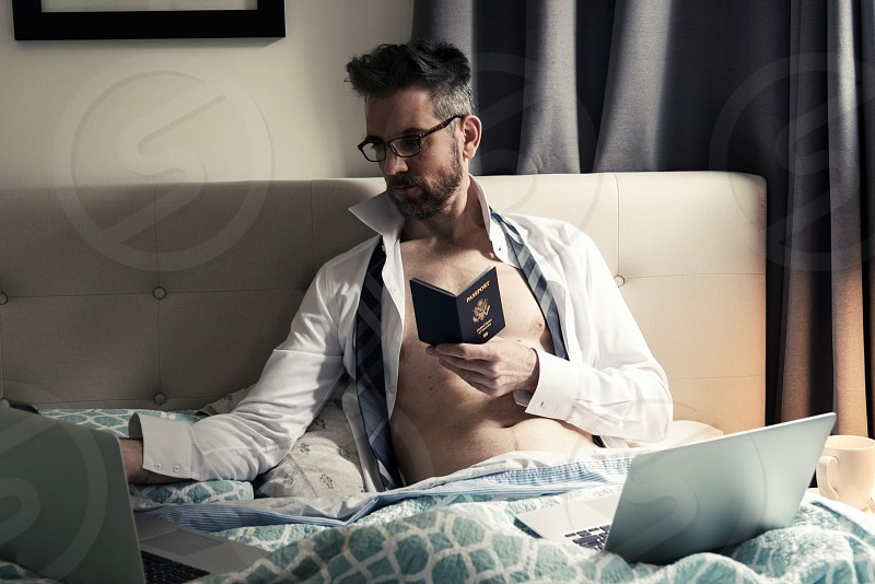 Handsome caucasian male in bed holding his passport using laptop computers to plan travel. photo