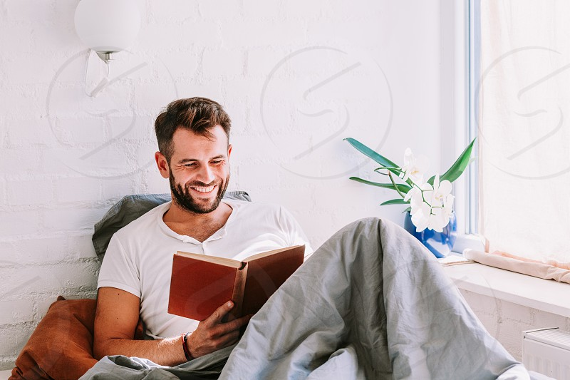 Young man reading a book in the bed photo