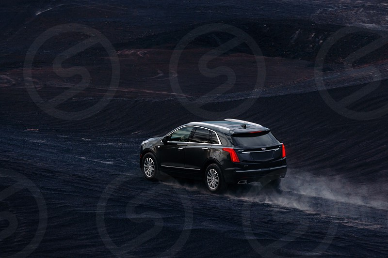 Cadillac XT5 shot on black volcanic rock sand outside Los Angeles photo